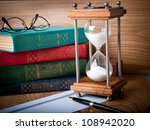 Hourglasses and book on a wooden table - stock photo