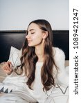 Small photo of young cute sleepy girl with long hair sitting in bed early in the morning, awake and stretching