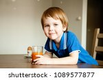 cute boy drinks pumpkin juice... | Shutterstock . vector #1089577877