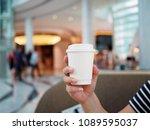 holds paper glass of hot green... | Shutterstock . vector #1089595037