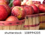 red ripe apples in bushel baskets at the farmer's market - stock photo