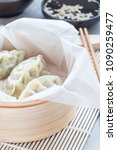 Small photo of Steamed Korean dumplings Mandu with chicken meat and vegetables in a bamboo steamer, vertical
