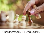 woman playing chess and hold queen - stock photo