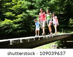 Family Walking On A Bridge In...