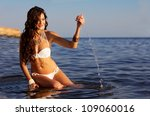 Bright portrait of a brunette resting in the water - stock photo