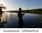 fisherman standing in the lake... | Shutterstock . vector #1090669313