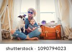 Small photo of Young girl with little baby and a dog sitting next to suitcase before travel near a window at home