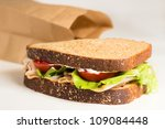Delicious turkey sandwich with lettuce, mayonnaise and tomato from brown bag lunch - stock photo