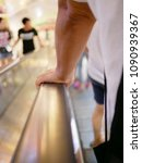 Small photo of A man's left hand holding on to an escalator handrail while moving to the lower floor