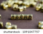 Small photo of Word TREND made from small golden letters on the brown background, selective focus