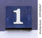 house number one on a makeshift wooden placard - stock photo