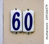 house number sixty on two separate enameled plates. Blue lettering on a white background. - stock photo