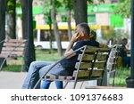 a man is sitting on a bench in... | Shutterstock . vector #1091376683