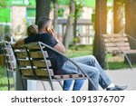 a man is sitting on a bench in... | Shutterstock . vector #1091376707
