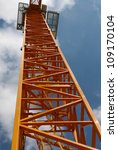 Orange crane used in the construction of buildings - stock photo