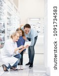 Small photo of Interesting fact. Energetic female pharmacist having conversation with family while using tablet