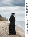 Small photo of Plague doctor in seaside. Outdoor portrait with dramatic sky in background.
