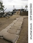 Small photo of Dikes or embankment built to prevent flooding from the river. Sandbags for flood defense . Sacks with sand to prevent a flood. Dangerous increase of water from rain storm. Dike keeps from flooding.