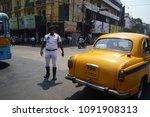 Small photo of Kolkata, India - March, 2014: Road police man trying direct traffic on the street near traditional retro cab in Calcutta