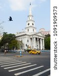 Small photo of Kolkata, India - March, 2014: Yellow taxi cab Ambassador on the crossroad in a front of old catholic St. Andrew's church in Calcutta