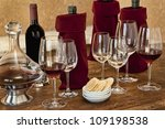 Wine tasting with bottles, glasses, crackers, on old wooden table - stock photo