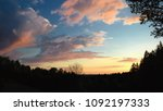 Beautiful sky with colorful clouds  and forest silhouettes within sunsetn evening landscape
