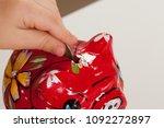 girl putting coins her piggy... | Shutterstock . vector #1092272897