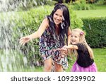 Beautiful young mother with her five years old daughter playing with fountain water in the park - stock photo