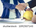 Small photo of Engineer and architect shake hands agree deal of big lot sales that finish goal of construction plans of the company