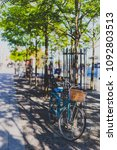 Small photo of DUBLIN, IRELAND - May 16th, 2018: detail of Grand Canal Square with trees, bikes and pedestrian on the affluent side of Dublin Docklands