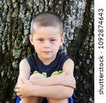 little boy sitting outside...   Shutterstock . vector #1092874643