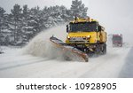 Heavy machinery cleaning road after snowstorm - stock photo