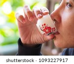 Small photo of Close-up portrait of asia woman enjoy for taking a sip of chinese tea blurred background.