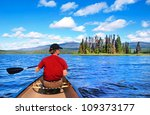 A Man Canoeing On A Lake In Th...