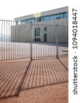 Small photo of Workplace Fenced a fence with light and shadow. large warehouse against a sunlight and sky.