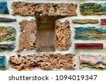 Small photo of A colorful stagger of rocks and bricks cemented as a unique design for a wall.