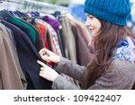Woman Choosing Clothes At Flea...