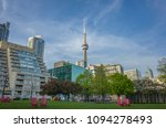 Small photo of TORONTO, CANADA - MAY 18, 2018: The CN Tower, new high - rise buildings, skyscrapers and Ann Tindal Park at sunset with a blue sky
