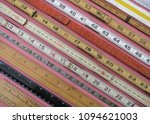 Small photo of Folding rulers and measuring tools in metric and inch measurement on a lively pink background suggest accuracy, precision and interest.