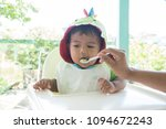 mom feeding food to baby | Shutterstock . vector #1094672243