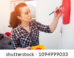 Small photo of Young dark-haired female artist in plaid shirt draws on a white wall a large red typewriter in a boy's room. Mom draw a brush with his son's car.