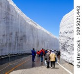 Small photo of Tateyama, Japan - May 28, 2017: tourists walking on the open part of the Road in the snow tunnel with 13 meter tall walls at Murodo plateau at Tateyama Kurobe Alpen Route