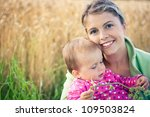Portrait of a mother and her baby girl outdoors - stock photo