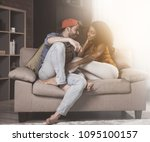Small photo of Happy together. Side view of positive romantic boyfriend and girlfriend are sitting on comfortable couch and talking. They are looking at each other with adoration. Sunlight in background