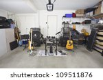 Rock band music equipment in a cluttered suburban garage. - stock photo