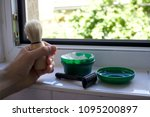 Small photo of beard shaving tools on a windowsill. hand holding shave brush. Razor and shave cream in background.