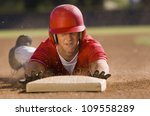 Young baseball player sliding towards second base on field - stock photo