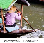 Small photo of Peasant is paddling boat in the rain. The folkway of Thai upcountry, live along river or canal.