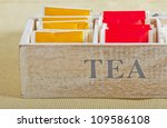 Yellow and red tea bags in a wooden box - stock photo
