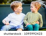 two blond hair brothers huging... | Shutterstock . vector #1095992423
